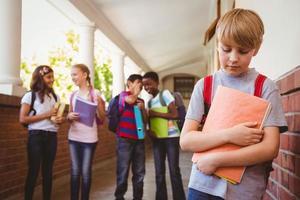 triest schooljongen met vrienden op achtergrond op school gang