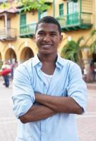 knappe jongen in blauw shirt in kleurrijke koloniale stad foto