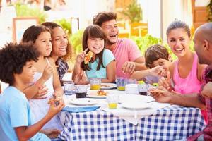 multi-etnische families eten in een openlucht restaurant foto