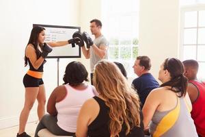 fitnessinstructeur die mensen met overgewicht aanspreekt bij de dieetclub foto