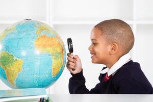 schooljongen met vergrootglas kijken naar globe foto