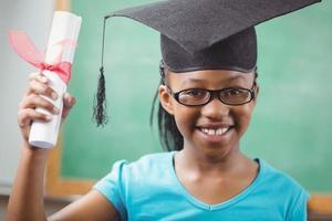 lachende leerling met mortel board en diploma foto