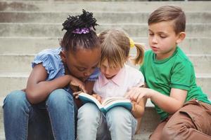 studenten zitten op stappen en een boek lezen foto