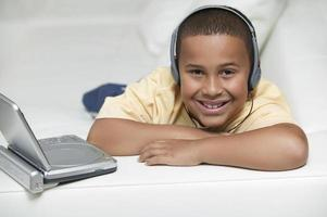 lachende jongen kijken naar draagbare dvd-speler