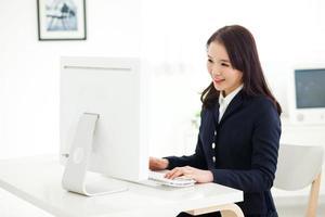 gelukkige Aziatische jonge vrouw die computer met behulp van. foto