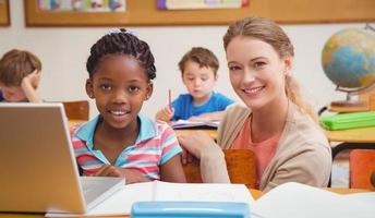 schattige leerling met behulp van computer met leraar foto