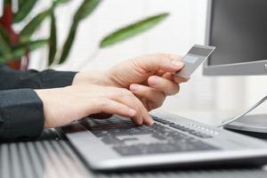 man gebruikt creditcard en computer voor online betaling. foto