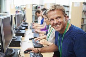 groep volwassen studenten die werken op computers foto