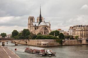 Notre Dame met toeristische boot op Seine in Parijs foto