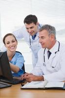 glimlachende chirurg die met artsen aan computer werkt foto