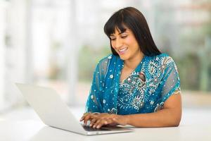 jonge Indiase vrouw met behulp van computer thuis foto