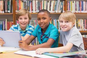 schattige leerlingen met behulp van tablet-computer in de bibliotheek foto