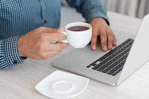 man aan het werk op een laptop en koffie drinken foto