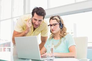 mooie ontwerper met hoofdtelefoon die op computer werkt foto