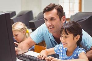schattige leerling in de computerklas met leraar foto
