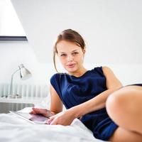 mooie, jonge vrouw met behulp van haar tablet-computer foto