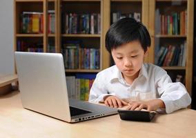 Aziatische jongen voor laptop computer foto