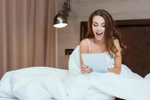vrolijke vrouw met behulp van tablet-computer op het bed foto