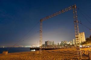 grote metalen frame op het strand 's nachts foto