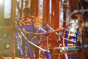 kleine jongen klimmen in avonturenpark foto