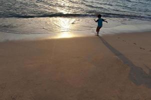 jonge jongen die op een Hawaiiaans strand loopt.