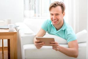 man met gadget om thuis te zitten foto