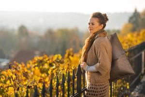 jonge vrouw in de herfst buitenshuis op zoek naar afstand foto