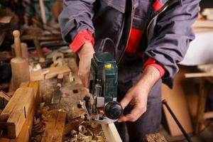 timmerman aan het werk met elektrische schrijnwerkerij foto