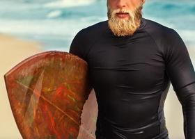 surfer aan zee staat met een surfplank