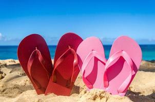 rode en roze slippers op het zandstrand foto
