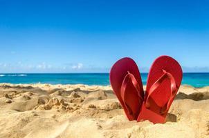 rode slippers op het zandstrand foto