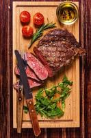 ribeye steak met rucola en tomaten.