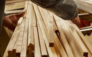 man aan het werk met houten planken foto