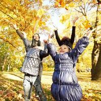 familie spelen met herfstbladeren foto