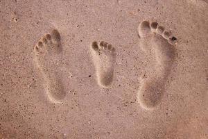 familie voetafdrukken in het zand foto