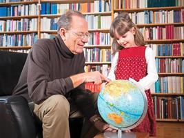 senior en kleindochter kijken naar een wereldbol foto