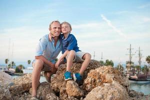 gelukkige vader en zoon in zonsondergang zeehaven