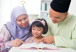 Maleisische moslimfamilie die een boek leest.