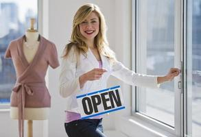 winkelier die open teken houdt foto