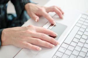 vrouwelijke handen die aan een laptop computertoetsenbord werken