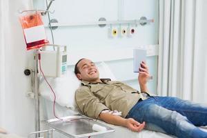 glimlachende getransfundeerde patiënt die een tabletcomputer bekijkt foto