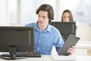 zakenman met digitale tablet die computer met behulp van bij bureau foto