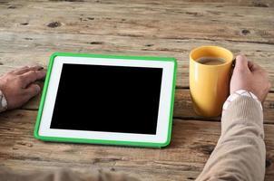 witte tabletcomputer met een kopje koffie foto