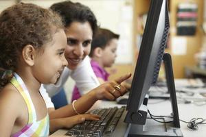 basisschoolleerlingen met leraar in computerklas foto