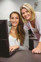 glimlachende leraar en student achter bureau bij computer foto