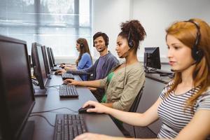 gelukkige student in computerklasse die bij camera glimlacht