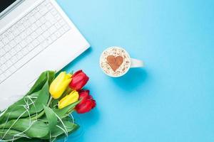 kopje cappuccino met hartvorm en computer foto