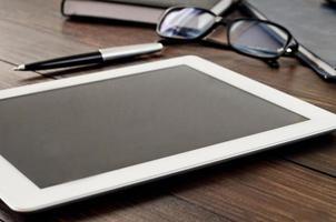 witte tabletcomputer op close-up van de bureau de houten lijst foto