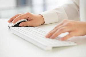 handen van een kantoor vrouw toetsenbord met creditcard te typen foto
