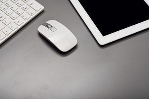 op een grijze ondergrond staat een tablet, toetsenbord en muis